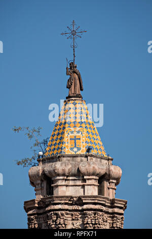 The tiled bell tower on the Baroque Churrigueresque style Iglesia del Carmen church and convent in the historic center on the Plaza del Carmen in the state capital of San Luis Potosi, Mexico. - Stock Image