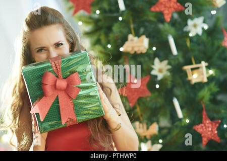 smiling young woman in red dress near Christmas tree hiding behind green Christmas present box - Stock Image