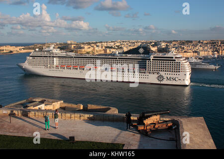 Mass tourism and travel in the Mediterranean Sea. The large cruise ship or liner MSC Orchestra departing from Malta's - Stock Image