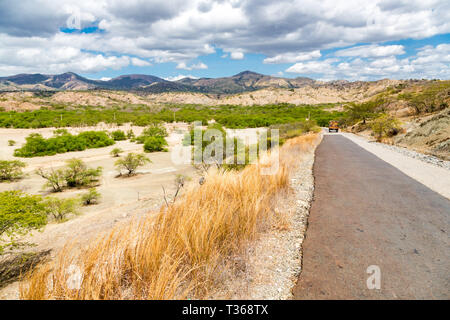 Asphalt road from Dili to Baucau with an orange truck in a distance. Dry savanna. Rural landscape, nature of East Timor or Timor-Leste, near Baucau, V - Stock Image