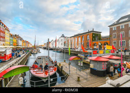 Tourists sightsee, board guide boats and dine at sidewalk cafes on an autumn day on the 17th century waterfront canal Nyhavn in Copenhagen, Denmark. - Stock Image