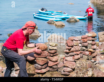 Dunbar, East Lothian, Scotland, UK. 21st Apr 2019. European stone stacking championship: Jonathon Kitching, from Aboyne in Scotland balances stones in the   artistic competition, giving competitors 3 hours to create anything from stones or found objects at Eye Cave beach on the second day which comprises 2 competitions, a 3 hour artistic challenge and a children's competition. The overall winner receives a trip to llano Earth Art Festival & World Stone Balancing competition in Texas in 2020. Credit: Sally Anderson/Alamy Live News - Stock Image