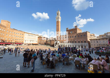 Tourists at a cafe in the Piazza Del Campo, with the Palazzo Pubblico and Torre del Mangia,  Siena Italy Europe - Stock Image