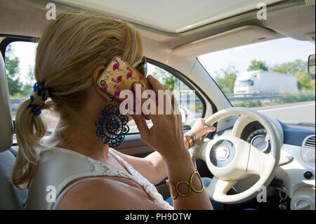 BOTTROP, GERMANY - AUG 16, 2018: A blond woman is calling with her smartphone while she is driving on a highway in full speed. - Stock Image