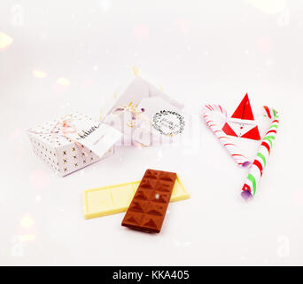 Christmas decoration with square gift box with dark and white chocolate and candy cane for celebration with confetti - Stock Image