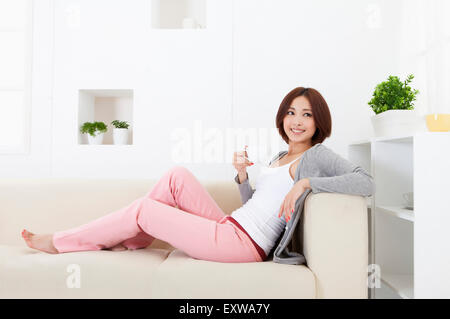 Young woman sitting on sofa and holding a cup with smile, - Stock Image