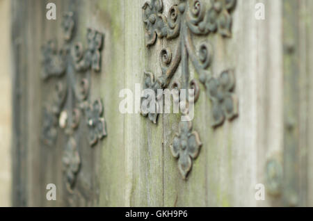 Decorative metal work on a wooden door. - Stock Image