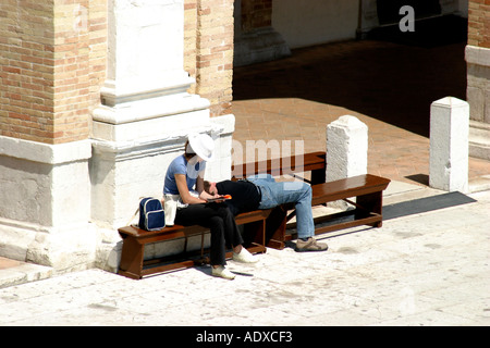 Couple of tourists  resting on a bench in the piazza of the important  Loreto Basilica in Le Marche Italy - Stock Image