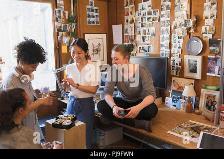 Creative designers eating sushi in office - Stock Image