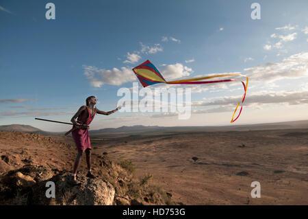 Maasai Warrior Flying Kite Over Ridge with Beautiful Scenic View - Stock Image