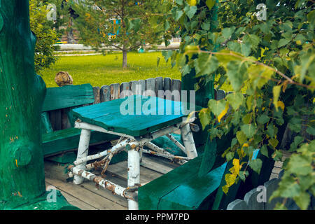 A table of birch tree trunks with black stripes and green boards with two benches - Stock Image