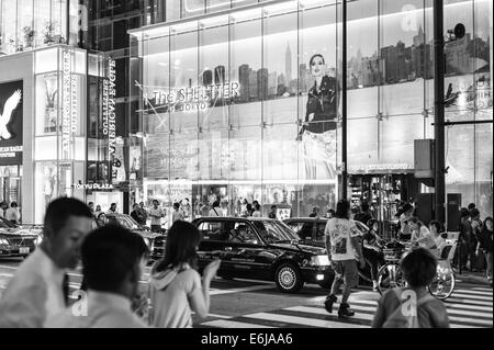 Reflections of shop signs on a warm evening in the window of The Shelter in Omotesando, Tokyo. - Stock Image
