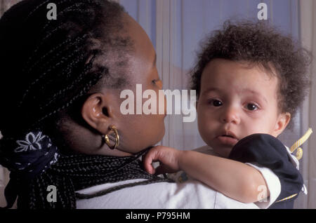 Black mother holding her unhappy mixed race baby girl - Stock Image