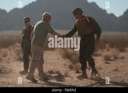 Brig. Gen. Roger Turner, Combat Center Commanding General, greets Jim Ricker, director, Government and External Affairs, prior to the ribbon cutting ceremony and live-fire demonstrations of the newly opened Johnson Valley Exclusive Military Use Area aboard the Marine Corps Air Ground Combat Center, Twentynine Palms, Calif., Aug. 24, 2018. The EMUA is open to all Marine Corps units and will allow for a more realistic level training that is capable of accommodating an entire Marine Air Ground Task Force. (U.S. Marine Corps photo by Sgt. Medina Ayala-Lo) - Stock Image