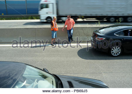 Two motorists pass the time as the westbound A1 autobahn is at a standstill (due to serious accident), near Haag in the Austrain state Lower Austria. - Stock Image