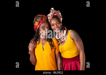Two African women in headscarves against a black background - Stock Image
