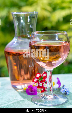 Wine carafe and glass with cold rose wine and wild flowers in summer sunny day in garden - Stock Image