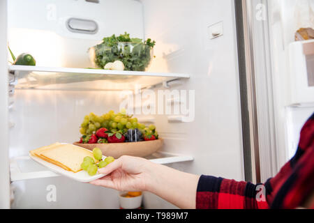 Woman takes cheese from fridge full of food. - Stock Image