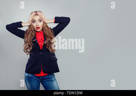 Shocked woman standing on gray banner background - Stock Image