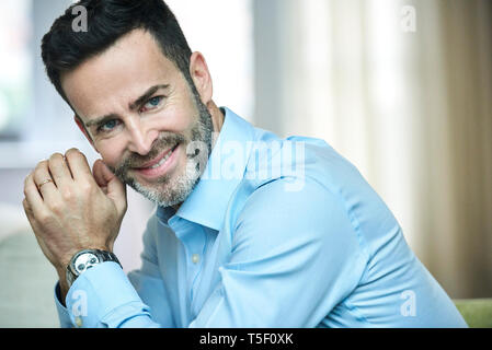 Smiling businessman sitting in hotel lobby - Stock Image