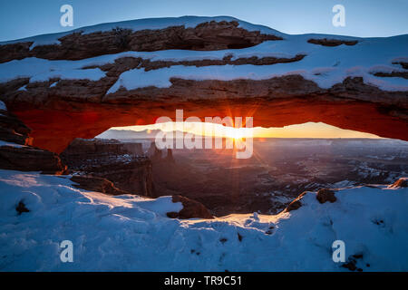 Mesa Arch under snow and sunburst, Island in the Sky District, Canyonlands National Park, Utah USA - Stock Image