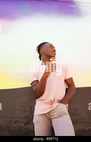 Young handsome black man wears a pink t-shirt, holds and eats a ice cream cone in summertime on a painted wall as a sunrise or sunny day - Stock Image