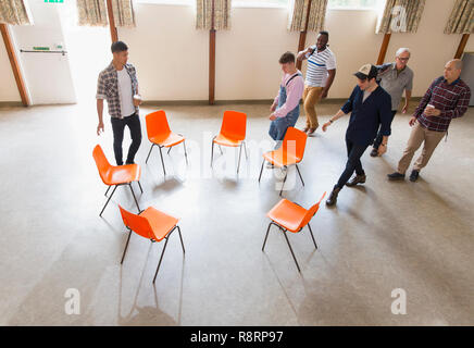 Men arriving at group therapy, sitting in circle in community center - Stock Image