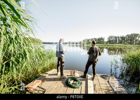 Landscape view on the beautiful lake and green reeds with two men fishing on the wooden pier during the morning light - Stock Image