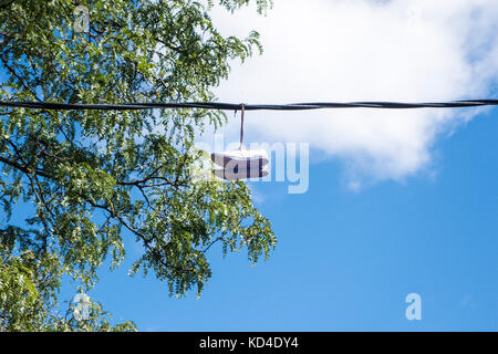 Running shoes hang over a telephone line in downtown Toronto Ontario Canada - Stock Image