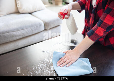 Woman splashes cleaning foam from white bottle on the wooden table and wipes it using blue cloth. - Stock Image