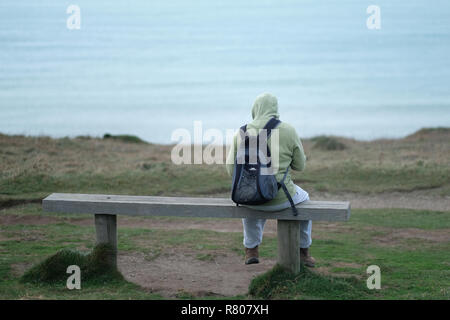 A figure sitting on a bench overlooking the sea in Porthtowan, ​Cornwall, UK. - Stock Image