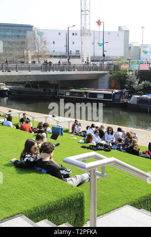 Relaxing on the steps leading down to the Regents Canal at Granary Square in spring sunshine, at Kings Cross, north London, UK - Stock Image