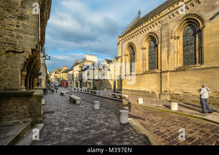 A tourist takes a photograph on a picturesque cobblestone street in Medieval Old Town Bayeux France. - Stock Image