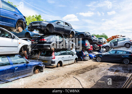 Cars with their wheels removed are stacked in piles of 3 cars with paths between them in a breakers scrap yard - Stock Image