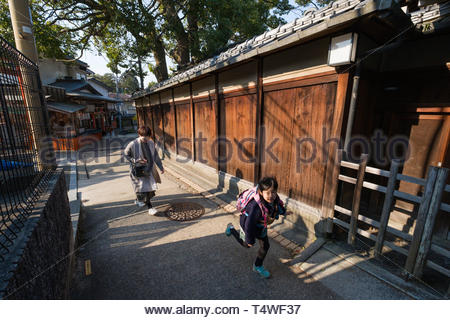Young girl wearing a pink backpack running to school in the early morning, Fukakusa Kaidoguchicho, Fushimi Ward, Kyoto, Honshu, Japan - Stock Image