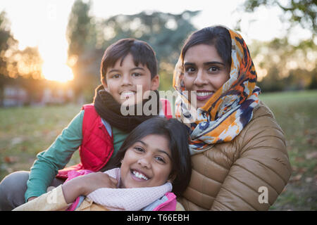 Portrait happy Muslim mother in hijab with children in autumn park - Stock Image