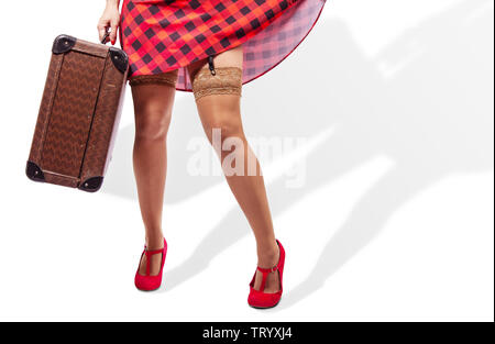woman in red dress and nylon stockings holding a suitcase isolated on  white. legs closeup - Stock Image