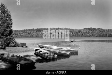 Boats and family rowing on Quebec Canada lake. - Stock Image