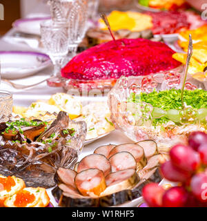 Snacks, fruits, sandwiches, salads, caviar and slicing on the holiday table - Stock Image