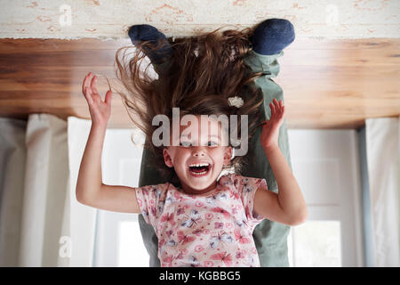 Girl being held upside down by her dad at home, low section - Stock Image