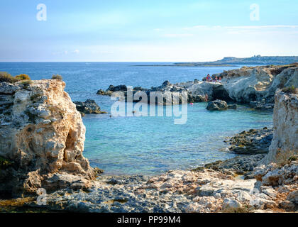 Blue water in a rocky cove near Ognina, Siracusa, Sicily, Italy - Stock Image