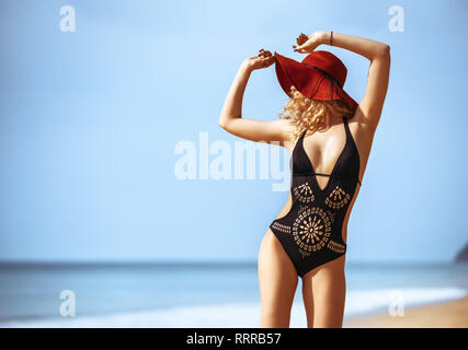 Beautiful lady stands in hat and dark swimsuit on tropical beach and smiling - Stock Image