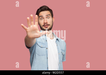 Stop it. Portrait of shocked handsome bearded young man in blue casual style shirt standing with stop hand sign and looking at camera. indoor studio s - Stock Image