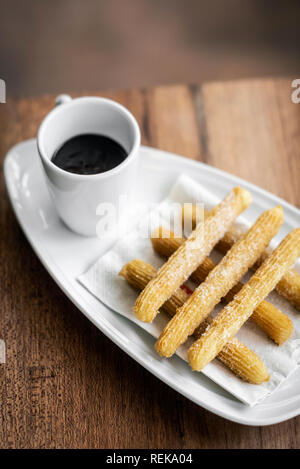 churros con chocolate traditional spanish sweet breakfast set on wooden table - Stock Image