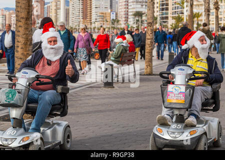 Benidorm, Costa Blanca, Spain, 25th December 2018. British tourists dress for the occasion on Christmas Day in this favourite getaway destination for Brits escaping the cold weather at home. Temperatures will be in the mid to high 20's Celsius today in this mediterranean hotspot. Two men on mobility scooters wearing Christmas clothing, santa hats and beards. - Stock Image