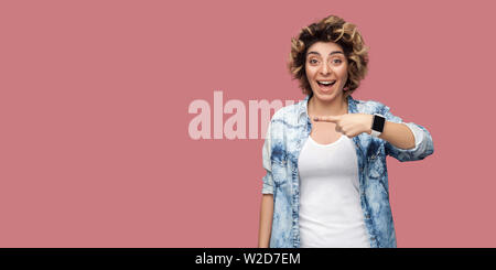 Portrait of amazed young woman with curly hairstyle in casual blue shirt standing and pointing at background empty copyspace with surprised face. indo - Stock Image