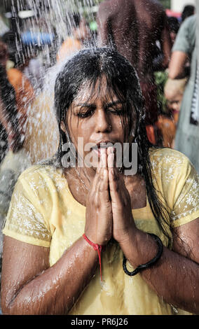 Woman worships under water shower during Thaipusam festival at Batu Caves in Selangor, Malaysia - Stock Image