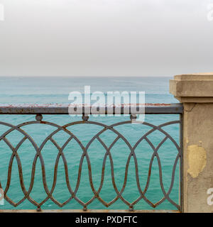 Rusted metal decorated protective fence of Stanley bridge at Alexandria, Egypt with Mediterranean Sea in the background - Stock Image
