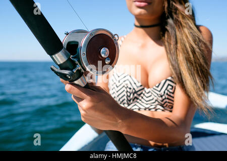 Close up of fishing reel and rod held by attractive young woman on fishing boat - Stock Image