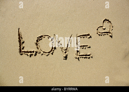 'Love' written out in wet sand. Please see my collection for more similar photos. - Stock Image